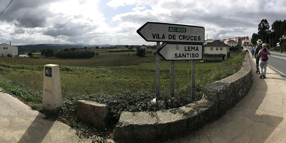 A sign with directions to vila de cruces and lema santiso