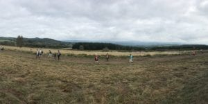 A panorama shot of the group walking in a field