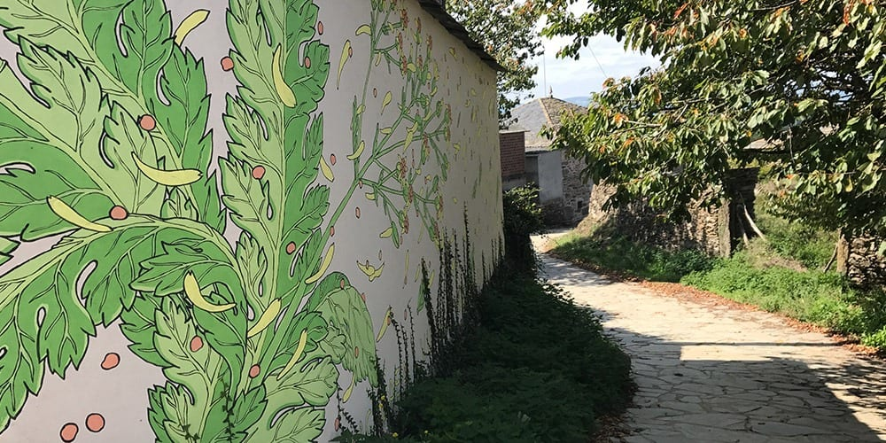 A wall mural of flowers and leaves next to a street